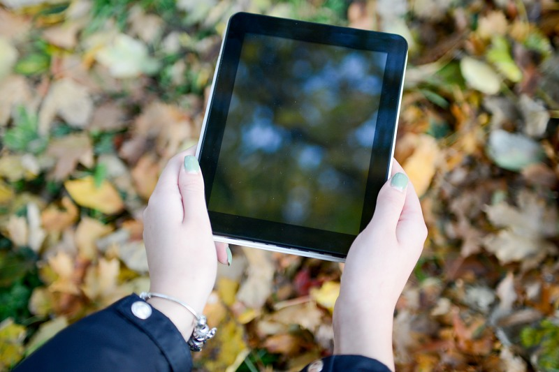 Girl looking at a tablet screen outdoor