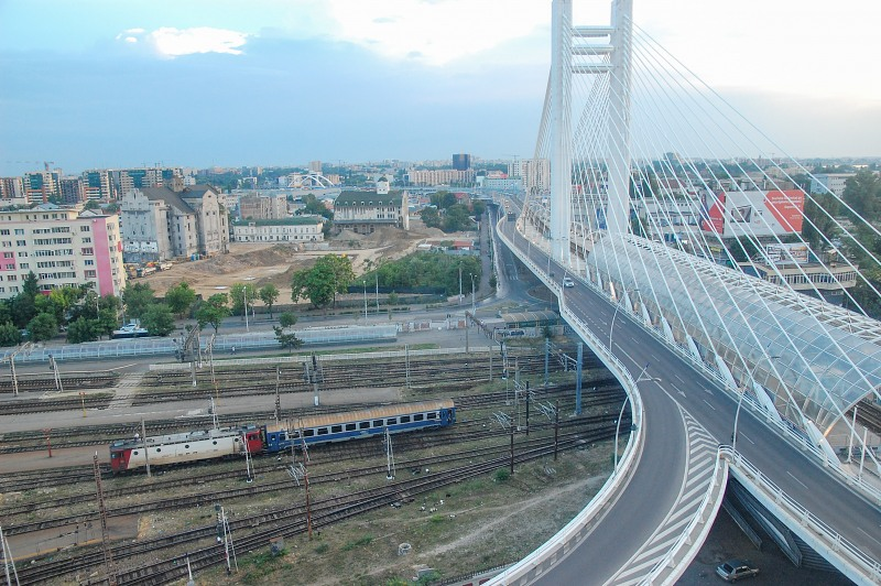 Train passing under modern suspension bridge in Bucharest