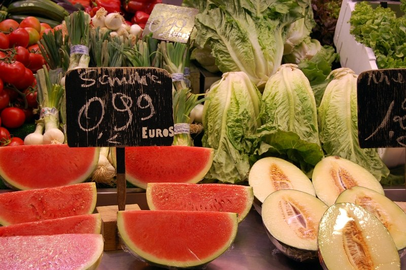 Watermelon and cantaloupe slices with various kinds of vegetables in background