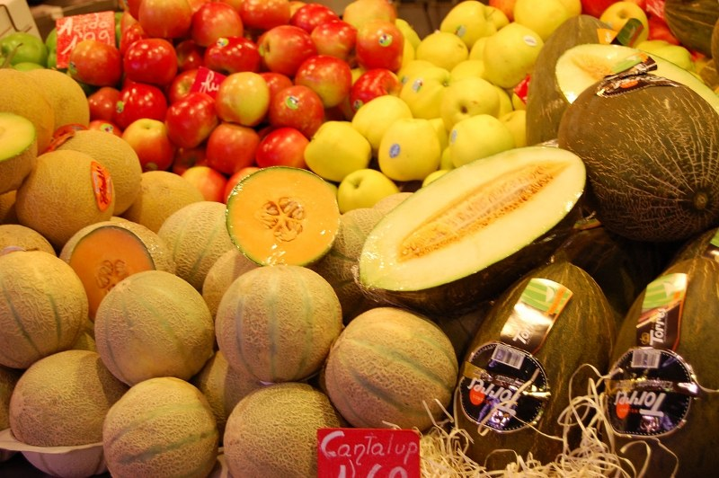Yellow melons and apples in piles