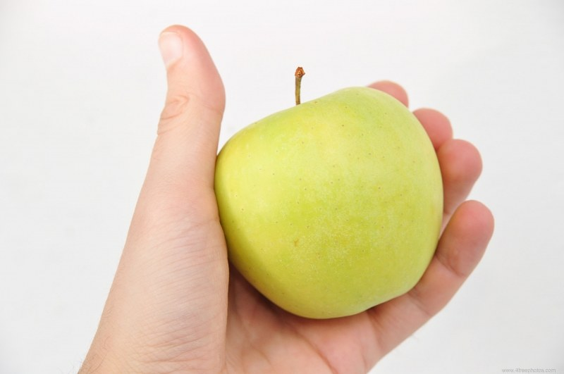 Hand with fresh green apple