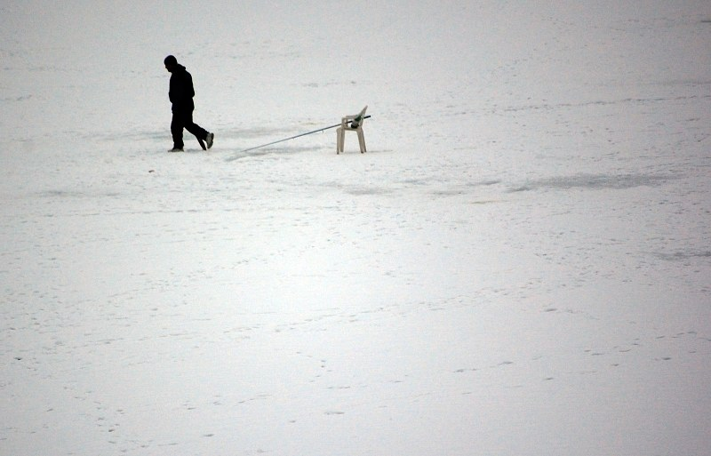 Man fishing on frozen lake