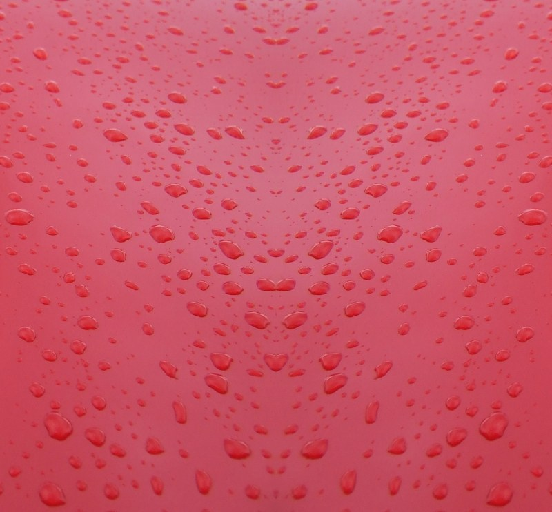 Water drops on red metal