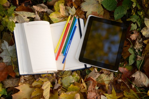 Student notebook with pens and tablet in forest