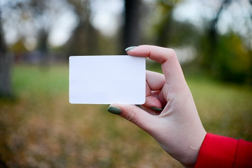Young woman holding a business card