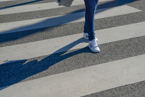 Young woman sport outfit walking on pedestrian crossing
