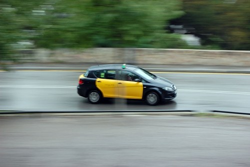 Black and yellow taxi passing in speed