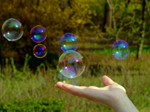 Hand holding a soap bubble