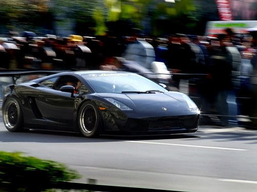 Sports car passing in front of a crowd