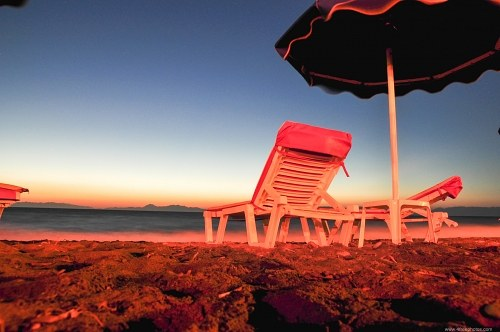 Beach umbrella and chairs sunset