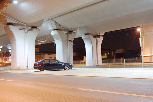 Car parked under bridge pylons