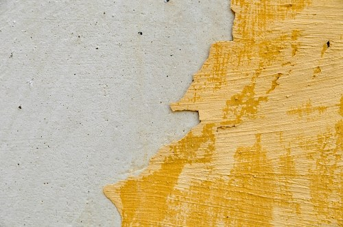 Concrete wall and fallen yellow plaster