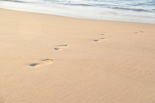 Footsteps on beach towards sea
