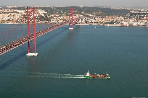 Large ship under ponte de 25 Abril in Lisbon