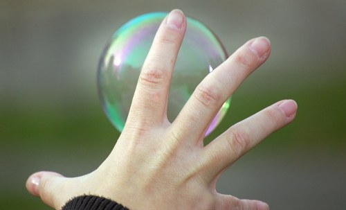 Hand reaching soap bubble