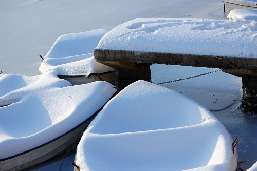 Snow covered boats on lake shore